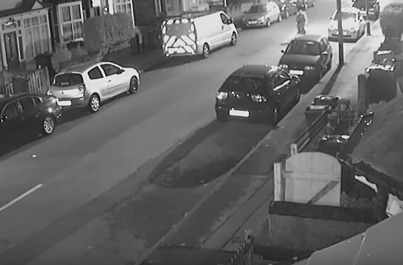 Dopey Cyclist Travels Down Road, Fails To Notice Parked Car Approaching